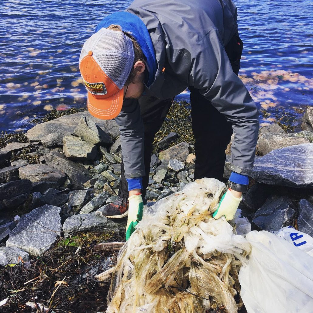An Impact Hub Bergen member cleans plastic waste from an island beach off the coast of Bergen.
